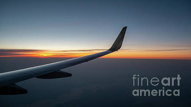 Right Wing of Airplane In Mid Air with Sunrise in the background by PorqueNo Studios