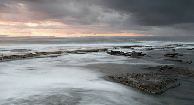 Rocky seashore seascape with wavy ocean during sunset  by Michalakis Ppalis