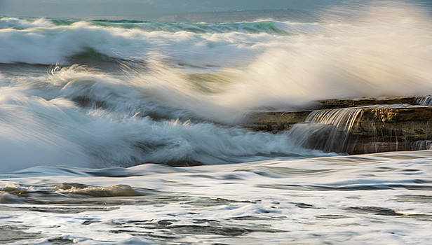 Rocky seashore with wavy ocean and wind waves crashing on the ro by Michalakis Ppalis