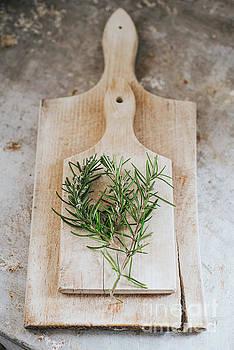 Rosemary on wooden board  by Viktor Pravdica