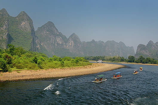 Reimar Gaertner - Row of tour boat rafts and a cruise ship heading up the Li river