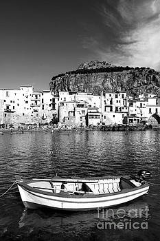 Rowboat along an idyllic Sicilian village. by Stefano Senise