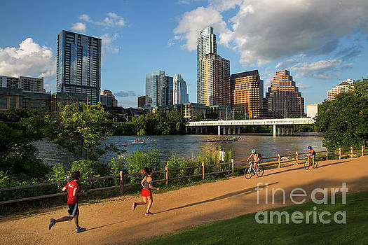 Herronstock Prints - Runners and bikers exercise on the hike and bike trail while rowing teams train on Lady Bird Lake