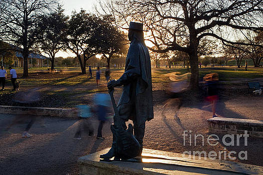 Herronstock Prints - Runners and joggers pass by the Stevie Ray Vaughan Memorial Statue at Auditorium Shores on Lady Bird Lake the afternoon sunsets