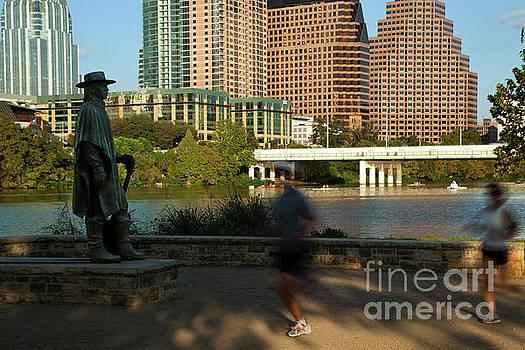 Herronstock Prints - Runners pass the iconic Stevie Ray Vaughn Memorial Statue Statue as kayakers paddle around Town Lake Austin
