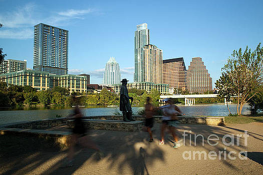 Herronstock Prints - Runners pass the Stevie Ray Vaughan Memorial Statue on Town Lake in downtown Austin, Texas