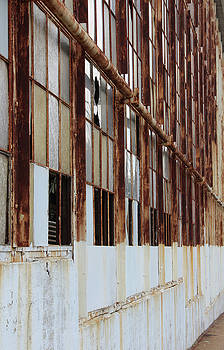 Rusted window frames of an abandoned building by Natalie Schorr
