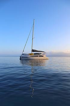 Sailing catamaran in early morning light in the Whitsundays by Keiran Lusk