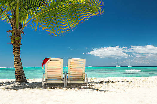 Santa's hat and sun loungers on the tropical beach by Valentin Valkov