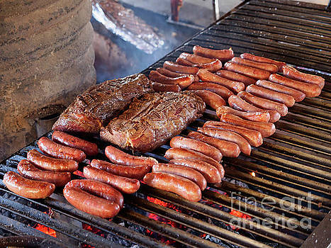 Sausages and beef on the grill at a traditional asado in Chile by Louise Heusinkveld