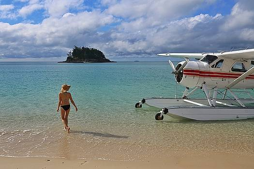 Sea plane and woman on beach in the Whitsundays by Keiran Lusk