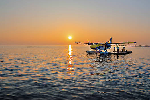 Seaplane and Sunrize above the ocean at Maldives by Yana Reint