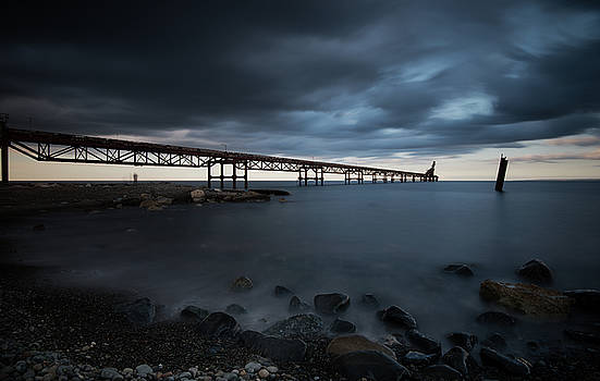 Seascape with jetty during a dramatic cloudy sunset by Michalakis Ppalis