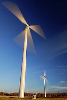 Reimar Gaertner - Several Large spinning Wind turbines against a blue sky