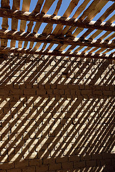 Reimar Gaertner - Shadow stripes of timber ceiling beams and slats on mud brick wa