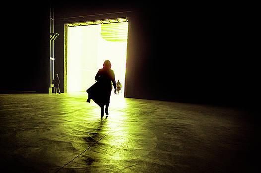 Silhouette of a business woman walking into the illuminated big  by Alfio Finocchiaro
