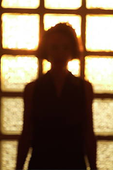 Sami Sarkis - Silhouette of a woman standing in front of a window
