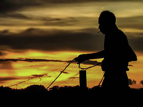 Silhouette of smoking fisherman with his net. by Sagar Lahiri