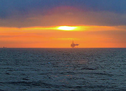 Silhouetted oil drilling platform  by Allan Levin