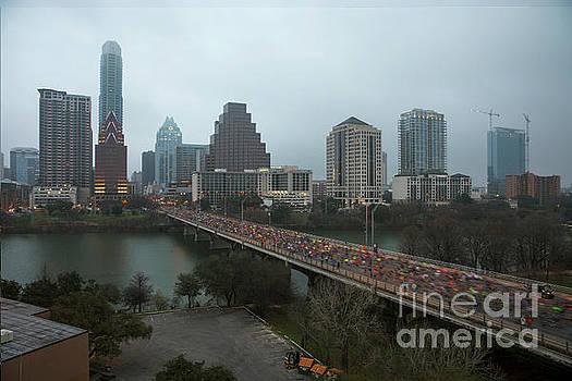 Herronstock Prints - Slow shutter shows blurred motion of the Austin Marathon runners on the Congress Avenue Bridge against the Austin Skyline after race start