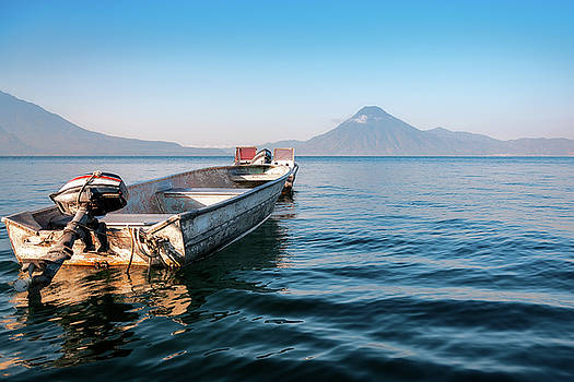 Small boat on the blue waters of Lake Atitlan by Daniela Constantinescu