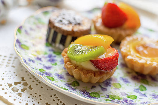 Small fruit tarts laid out on an antique china plate by Bradley Hebdon