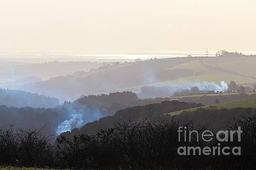 Smoke rising on hilly hazy landscape by Peter Noyce