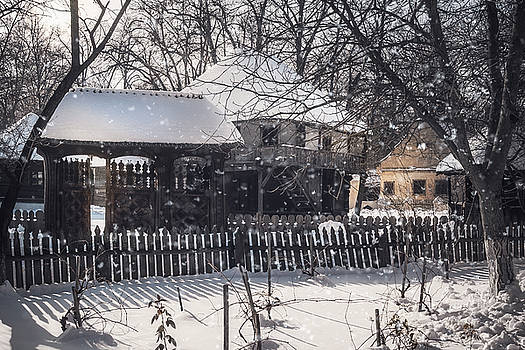 Snowfall over old traditional houses in a Romanian Village by Daniela Constantinescu