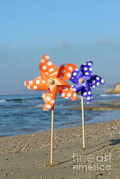 Spinning pinwheels on a beach by George Atsametakis