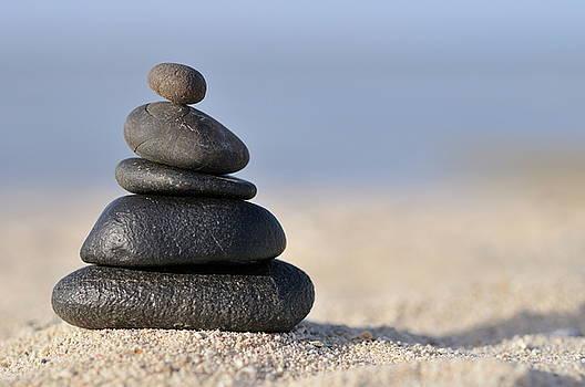 Sami Sarkis - Stack of black pebbles on beach