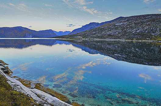 Stark mountains are reflected in the calm water of fjord Ejfjorden by Intensivelight