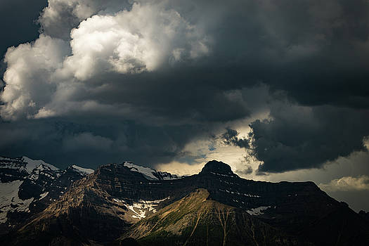 Storm clouds over snowy mountains in Banff National Park by William Freebilly photography