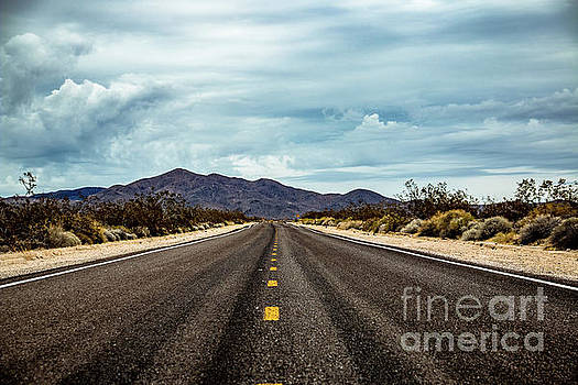 Straight road with mountains in the background and clouds by Amanda Mohler