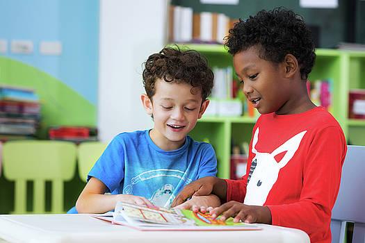 Student in international preschool reading a magazine book toget by Anek Suwannaphoom