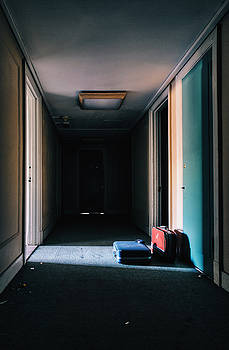 Suitcases in abandoned hotel hallway. by Dylan Murphy