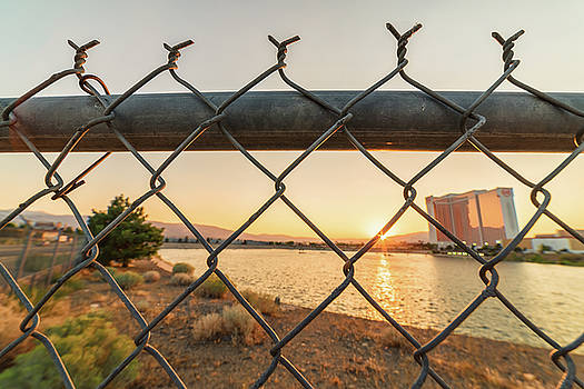 Summer Sunset Over MGM Lake Looking Through A Fence With Grand Sierra Resort In The Background by Brian Ball