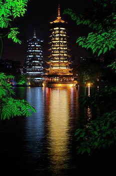 Reimar Gaertner - Sun and Moon Pagodas on Shanhu or Fir Lake at night framed by tr