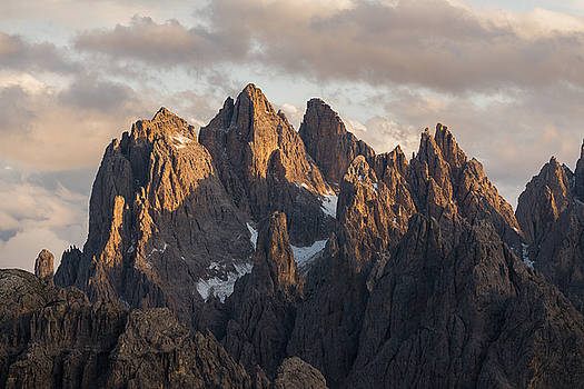 Sun illuminating peaks in the Dolomites mountains, Italy, Europe by Blaz Gvajc