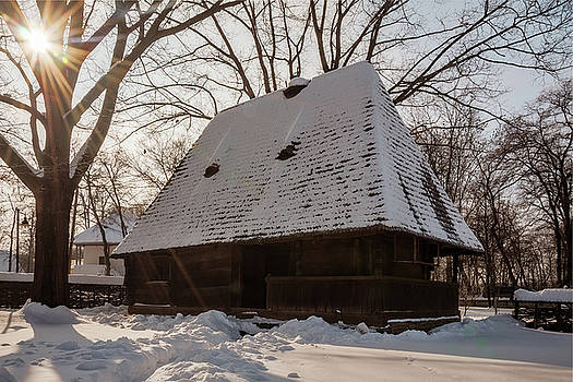 Sun shines over a snow covered traditional wooden homestead  by Daniela Constantinescu