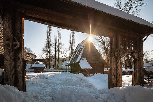 Sun star warming up a traditional Romanian homestead in winter by Daniela Constantinescu