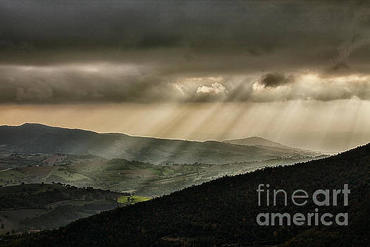 Sunrays illuminate hills and mountains by Luigi Morbidelli