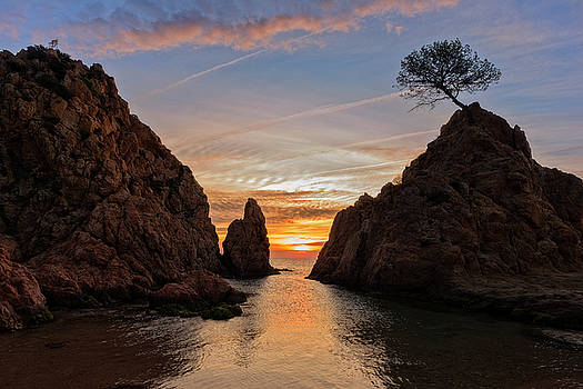 Sunrise on the mediterranean sea with the sun among the rocks by Vicen Photography