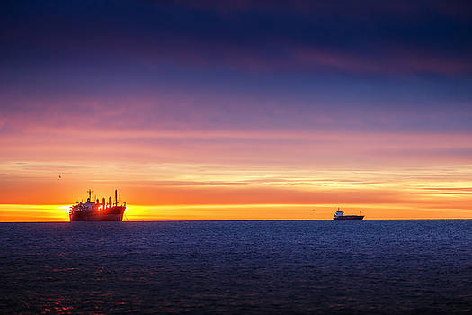 Sunrise over the sea with sailing cargo ship by Valentin Valkov