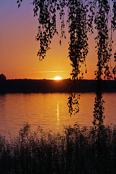 Sunset over lake by Jaroslaw Suchozebrski