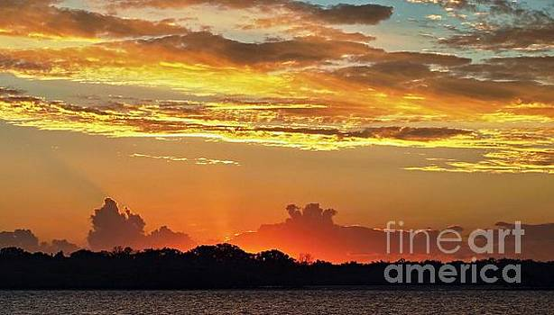 Sunset with high golden glow and crimson highliting and silhouet by Geoff Childs