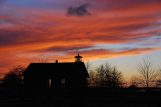 Sunsetting behind the historic Schoolhouse. by Wanda Jesfield