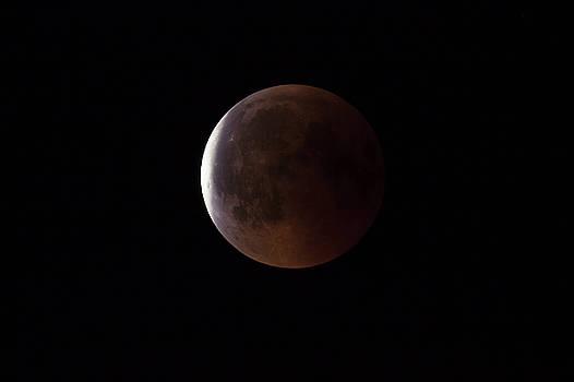 Super Bloody Moon, full eclipse end phase against black sky background by Lukasz Szczepanski