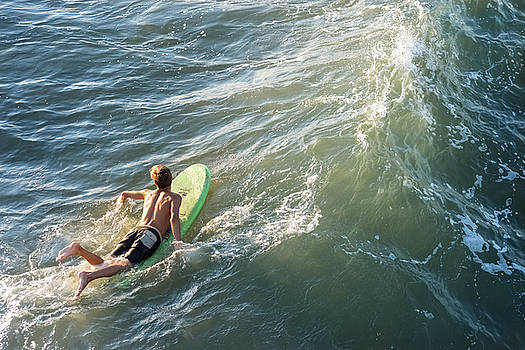 Surfer paddles out on surfboard without a wetsuit by Bradley Hebdon