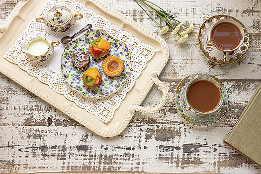 Tea cups and fruit tarts laid out on rustic table by Bradley Hebdon