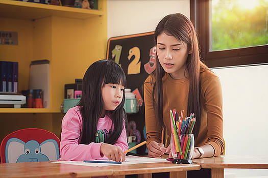 Teacher and student take home work togather in preschool by Anek Suwannaphoom